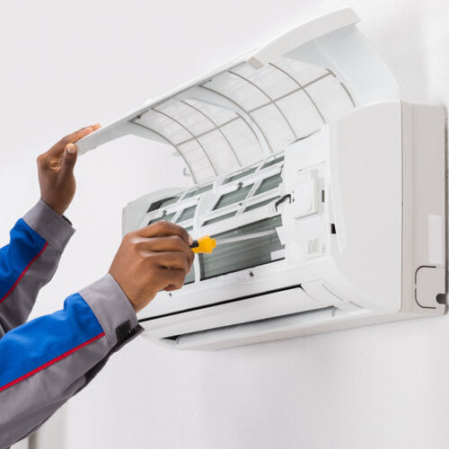 close up of technician repairing an AC mounted unit