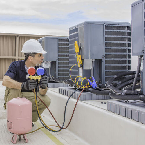 a technician servicing or charging a condensing unit with 410A refrigerant outdoors