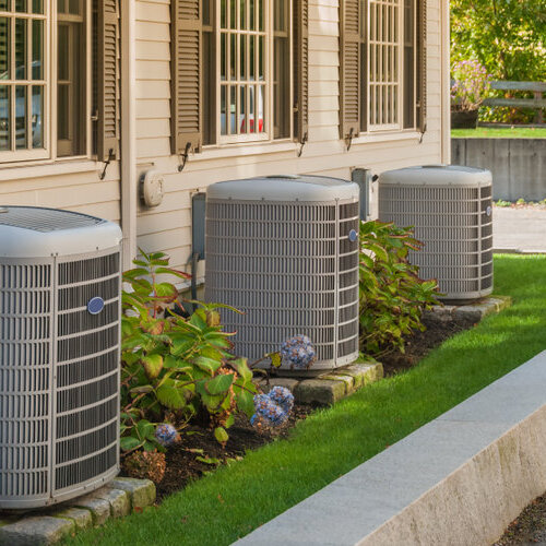 HVAC units outside home on lawn with plants