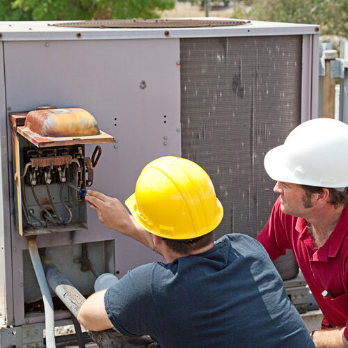two technicians repairing a commercial or industrial AC compressor on a rooftop