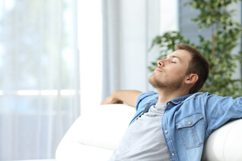 Man resting on a couch indoors breathing