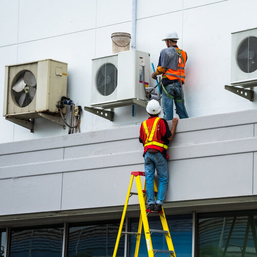 technicians on roof servicing air conditioning units